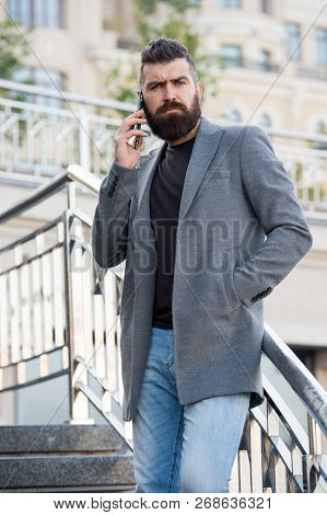 Stay In Touch. Man Bearded Serious Businessman Hold Mobile Phone Urban Background. Hipster Smartphon