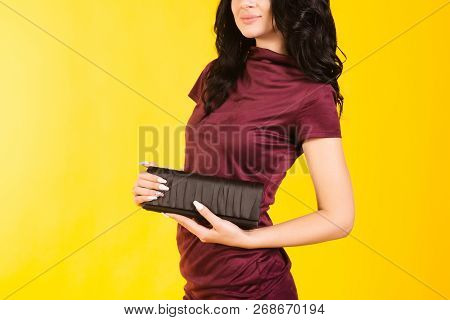 Stylish Girl In A Burgundy Dress Holding A Purse On A Yellow Background.