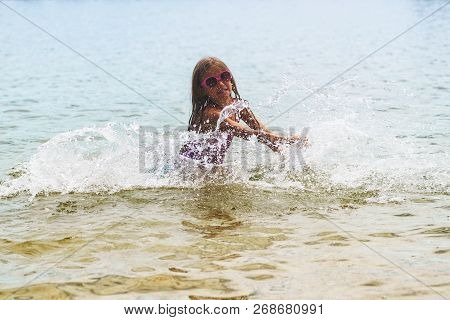 Happy Little Girl Playing In Shallow Water Waves.little Girl Playing In The Sea Waves, Girl Having F