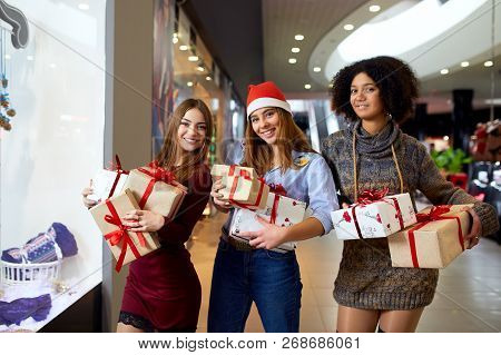 Three Mixed Race Women With Gift Boxes In Hands Near Storewindow. Multi Ethnic Girls Smiling With Pr