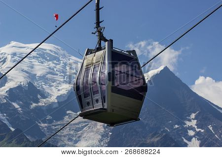 Mountain Trailer Funicular Gray Descends On The Background Of Snow-capped Peaks And A Mountain Valle