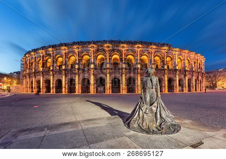 Nimes, France. Roman Amphitheater (arena Of Nimes) At Dusk And Monument To Bullfighter