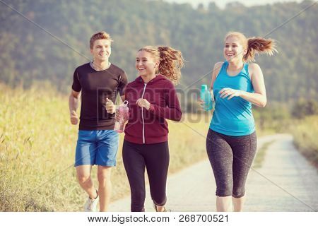 group of young people jogging on country road runners running on open road on a summer day