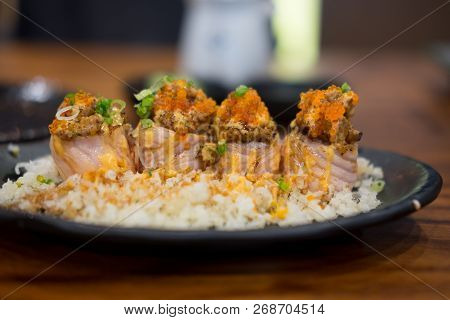 Close Up Of Grill Salmon Roll Sushi On Black Dish In The Restaurant (selective Focus)