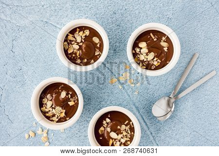 Homemade Chocolate Pudding In Three White Ceramic Ramekins With Roasted Almond Slivers And Teaspoons