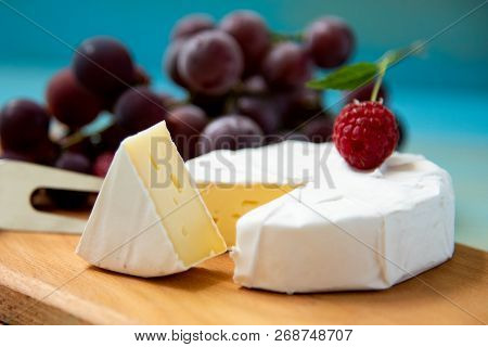 Cheese Camembert With Raspberries And Grapes On Table