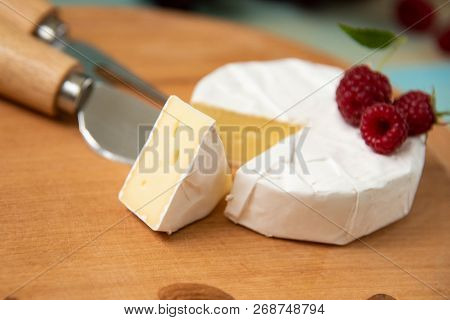 Cheese Camembert With Raspberries And Nuts On Table