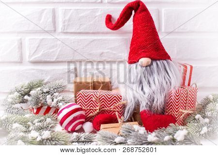 Winter Holidays  Decorations. Funny Elf, Wrapped Christmas Presents, Balls,  Fur Tree Branches On Wh