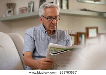 Portrait of elderly man reading newspaper while sitting on couch. Retired man wearing spectacles while reading news at home. Senior grandfather reading bad news.