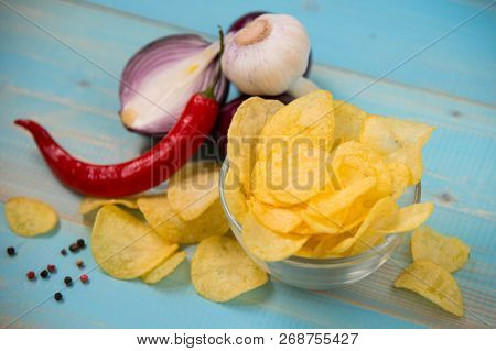 Potato Chips In Bowl On A Blue Wooden Background