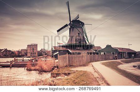 Old Wooden Windmill On Zaan River Coast, Zaanse Schans Town, Popular Tourist Attractions Of The Neth