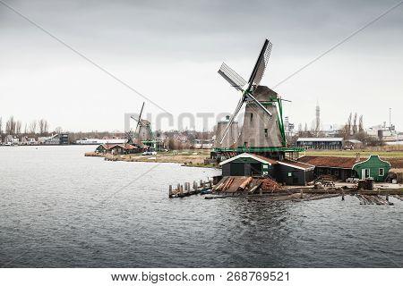 Windmills On Zaan River Coast. Zaanse Schans Town, Netherlands. Suburb Of Amsterdam