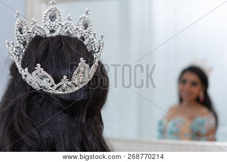 Young teen hispanic girl wearing a quinceanera dress