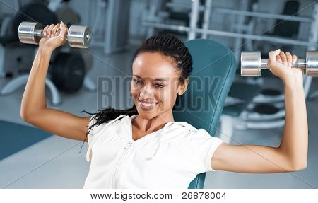 A young woman lifting free weights with a confident smile