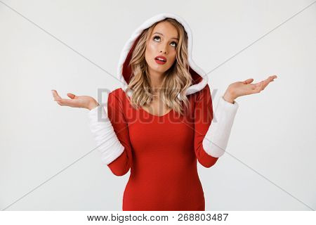 Portrait of a confused blonde woman dressed in red New Year costume standing isolated over white background, shrugging shoulders