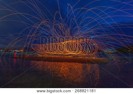 Reflection Of Spark Fire Swirl From Steel Wool With Long Exposure Speed Motion Abstract At Sunrise I