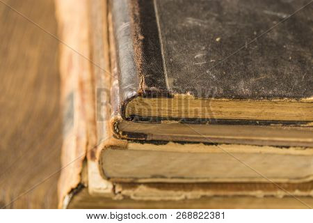 Ancient books lie in a pile. Leather bindings, worn covers, yellowed pages. poster