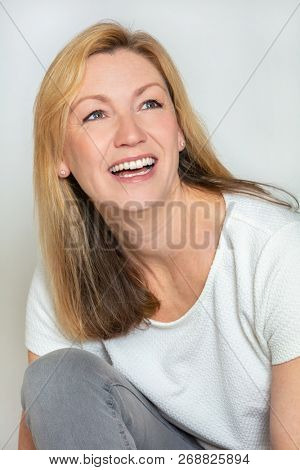 Studio portrait headshot of attractive happy middle aged blond woman in her forties