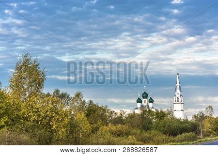 White-stone Orthodox Church With Green Domes Against A Cloudy Sky.