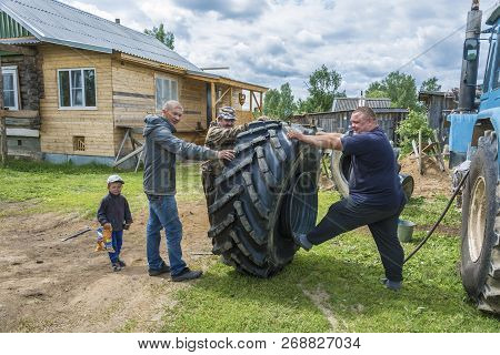 Yaroslavl Region, Russia - 06/11/2018: Three Men Assemble A Large Wheel From A Tractor On June 11, 2