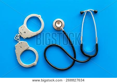 Medical Lawsuit. Arrest For Medical Crime Concept. Handcuff Near Stethoscope On Blue Background Top