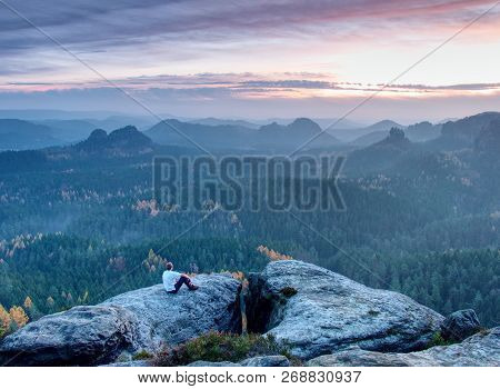 Hiker Is Enjoying Sunrise View In Hilly Landscape. Male Hiker Sitting And Relaxing At The Rocky Summ