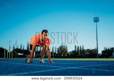 Young athlete man at starting position ready to start a race. Sprinters ready for race on race track. poster