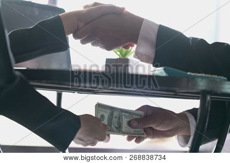 Corrupted Businessman Sealing The Deal With A Handshake And Receiving A Bribe Money, Anti Bribery An