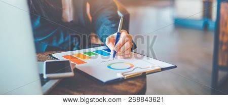Business Woman Hand Work On Charts And Graphs That Show Results.she Uses The Pen To Point To The Gra