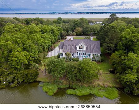 Aerial view of waterfront home on wooded property