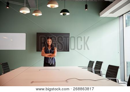 Portrait Of Young Businesswoman Standing By Boardroom Table At Graduate Recruitment Assessment Day In Office