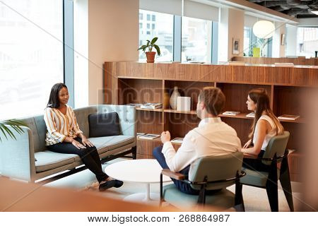 Businessman And Businesswoman Interviewing Female Candidate In Office At Graduate Recruitment Assessment Day