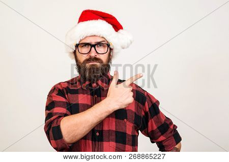 Handsome Bearded Man In Santa Hat And Glasses. Santa Man Pointing To The Side Over White Wall. Chris
