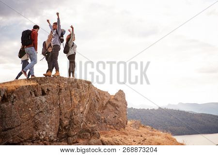 A group of five happy young adult friends cheer with their arms in the air at the summit of a mountain during a hike