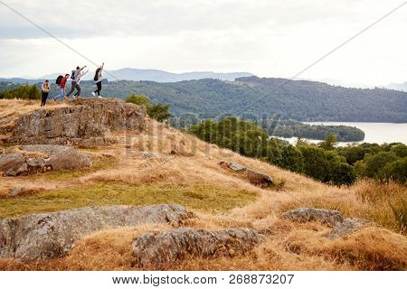 A group of five mixed race young adult friends arrive at summit with arms in the air after a mountain hike