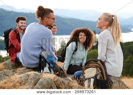Five young adult friends sit talking at the summit after a mountain hike, close up