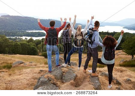 A group of five young adult friends celebrate arriving at the summit after a mountain hike, back view