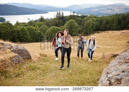Multi ethnic group of five young adult friends hiking across a field uphill towards the summit, front view poster