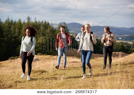 Multi ethnic group of five happy young adult friends walking on a rural path during a mountain hike, close up poster