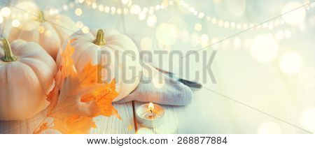 Thanksgiving Day dinner. Holiday served table decorated with pumpkins, autumn bright colorful leaves and burning cadles. Beautiful table setting, Thanksgiving backdrop, widescreen background