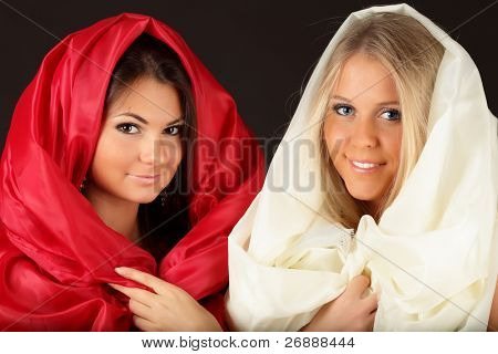 2 women wrapped in fabric on black background
