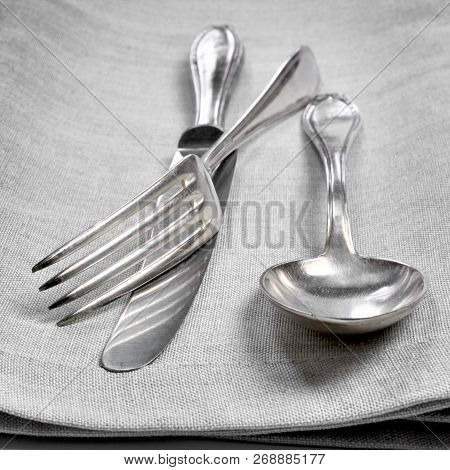Vintage Cutlery, Silverware. Old Silver Cutlery On A Cloth Or Serviette Background. Top View Of Tabl
