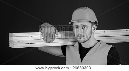 Carpenter, Woodworker, Strong Builder On Thoughtful Face Carries Wooden Beam On Shoulder. Man In Hel