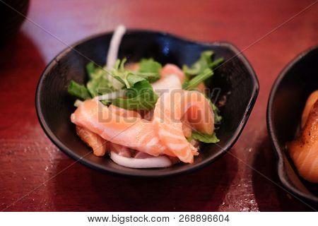 Salmon Sashimi Spicy Salad On Black Dish (japanese Food)
