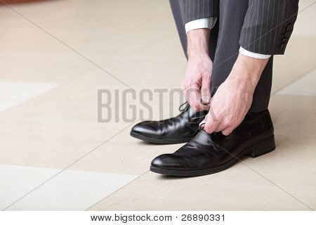 Man ties his shiney new black leather business shoes.