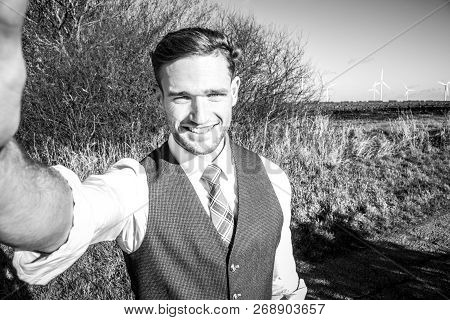 Handsome Man Dressed In A Suit Taking Selfie With Countryside And Trees In Background