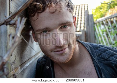 Portrait Of Handsome Red Head Man With Open Leather Jacket And Stubble Looking At Camera