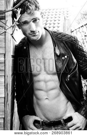 Handsome Blonde Man With Open Leather Jacket Revealing Sixpack Abs And Looking At Camera