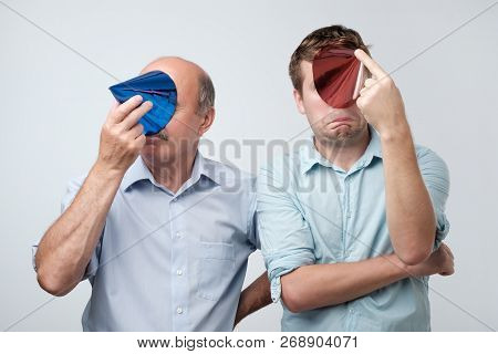 European Mature Father And Son Hiding Their Face With Birthday Cap After Great Party