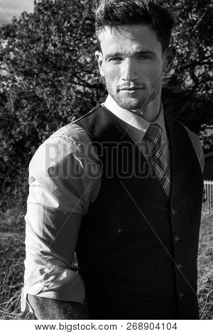 Good Looking Man Dressed In A Suit In Countryside With Trees And Fields Behind Behind Him